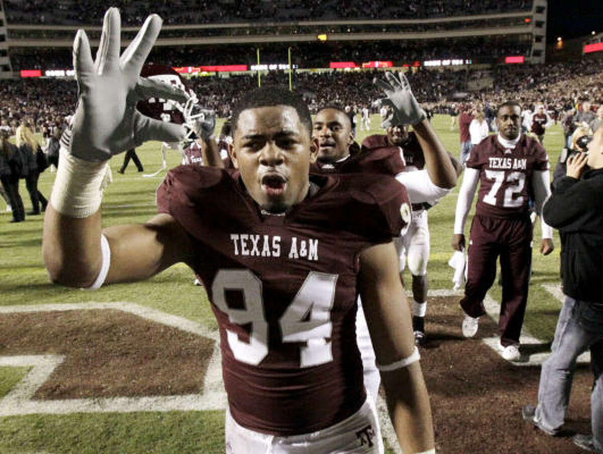 Texas A&M defensive tackle Damontre Moore (94) makes a symbol for the