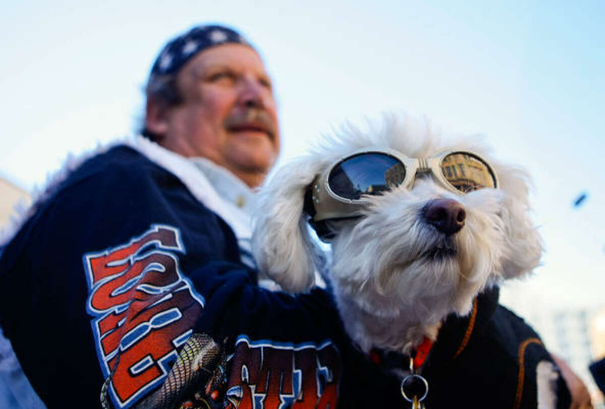 Annie and her owner, Kenneth Looney, of Dallas, watches the parade of motorcycles at the Lone Star Rally. The event celebrates