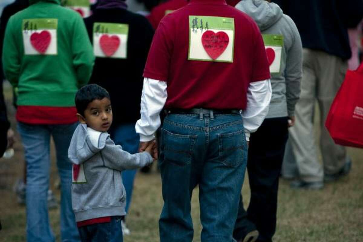 Hand-in-hand with his father, Honorato Villafranco, of Fort Worth, Cesar Villafranco, 4, looks back as his family walked in honor of Cesar's aunt Gracie Madrigal during 2010 Start! Houston Heart Walk five-mile walk down Allen Parkway benefiting the American Heart Association. The event is the largest annual fundraiser of the year where about 25,000 walkers helped raise more than $1.5 million for those who suffer from heart disease and for the American Heart Association. The event had booths focusing on heart health and healthy living.