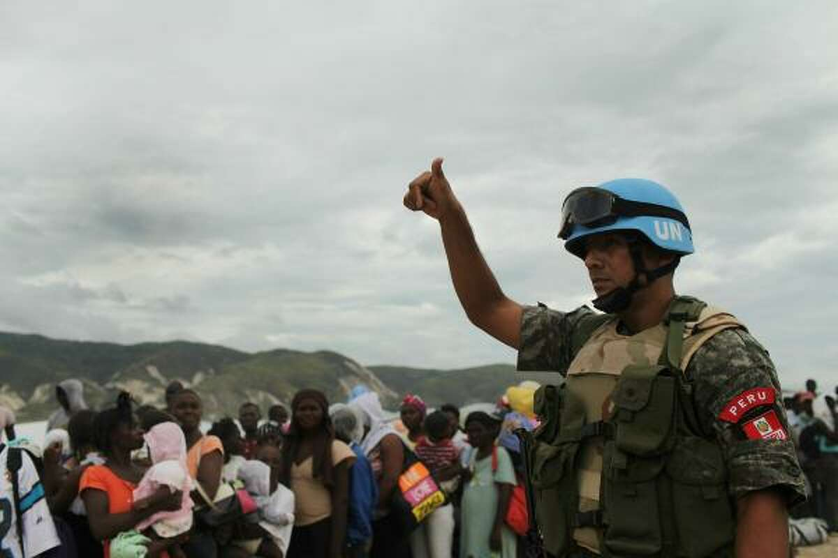 A United Nations peacekeeper stands beside people waiting for U.N. trucks during the evacuation of over 1,000 of the most vulnerable residents of the Corail-Cesselesse relocation camp.