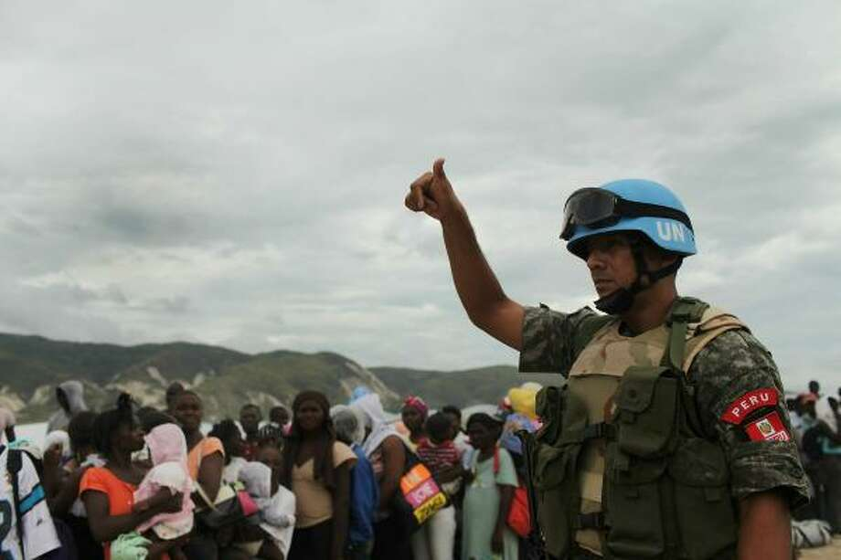 The Nobel Peace Prize 1988 was awarded to United Nations Peacekeeping Forces.In this photo, a United Nations peacekeeper stands beside people waiting for U.N. trucks during the evacuation of over 1,000 of the most vulnerable residents of the Corail-Cesselesse relocation camp. Photo: Spencer Platt, Getty Images