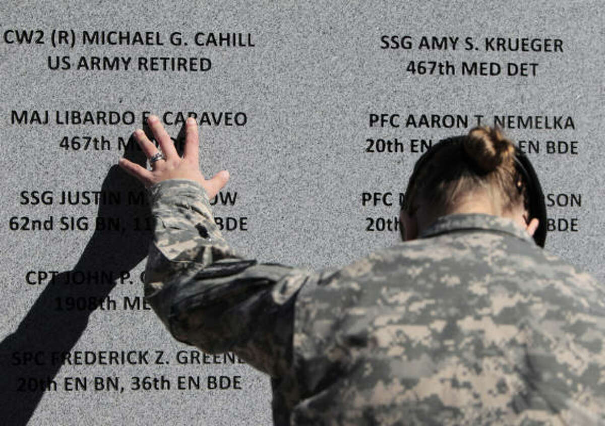 Staff Sgt. Joy Clark of the 467th Combat Stress Control Detachment takes a moment to run her fingers over the engravings of the names of her fellow soldiers at a ceremony to unveil a memorial to those killed in the Fort Hood, Texas, massacre. A ceremony on Friday, November 5, 2010, at Fort Hood marked the one-year anniversary of the shooting, and soldiers and civilians were also recognized for their heroic actions on the day of the massacre.