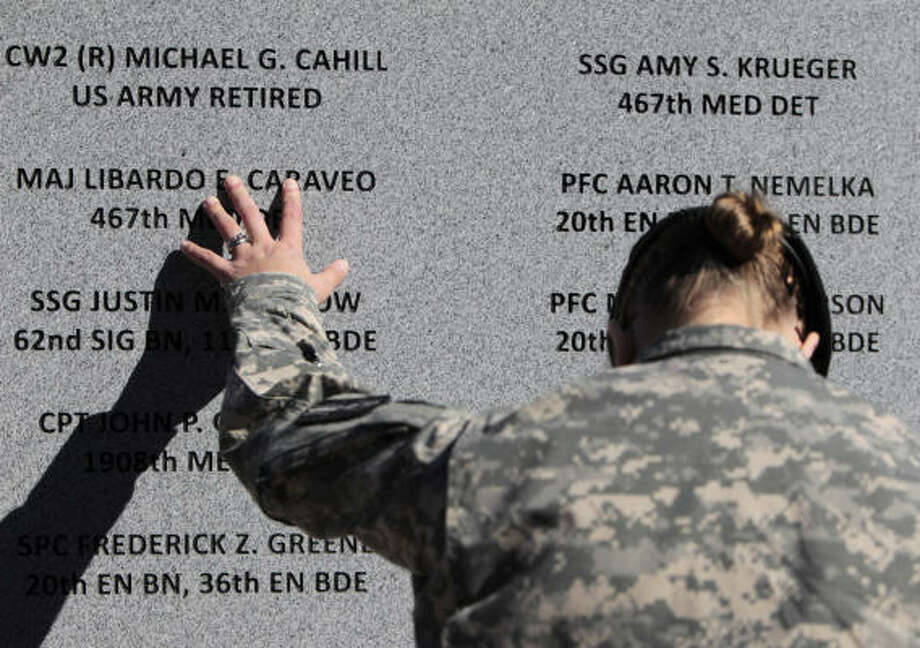 Staff Sgt. Joy Clark of the 467th Combat Stress Control Detachment takes a moment to run her fingers over the engravings of the names of her fellow soldiers at a ceremony to unveil a memorial to those killed in the Fort Hood, Texas, massacre. A ceremony on Friday, November 5, 2010, at Fort Hood marked the one-year anniversary of the shooting, and soldiers and civilians were also recognized for their heroic actions on the day of the massacre. Photo: SONYA N. HEBERT, MCT