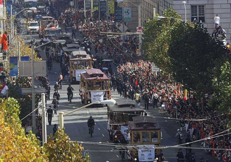 The San Francisco Giants ride in motorized cable cars during Wednesday's parade through downtown San Francisco. The city celebrated its first World Series title. Photo: Mike Adaskaveg, AP