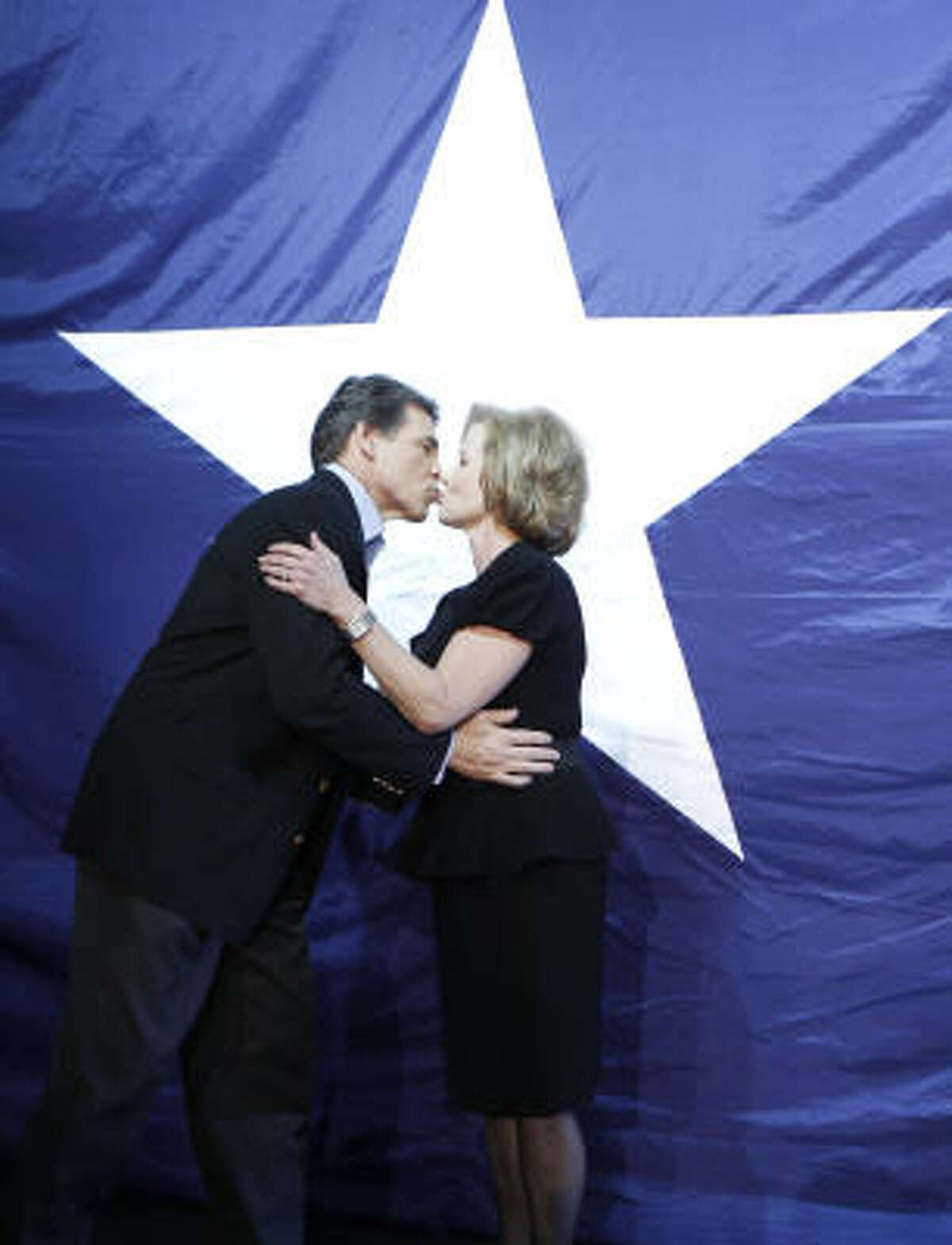 Texas Republican Gov. Rick Perry, left, kisses his wife Anita Perry at his victory party, Tuesday.