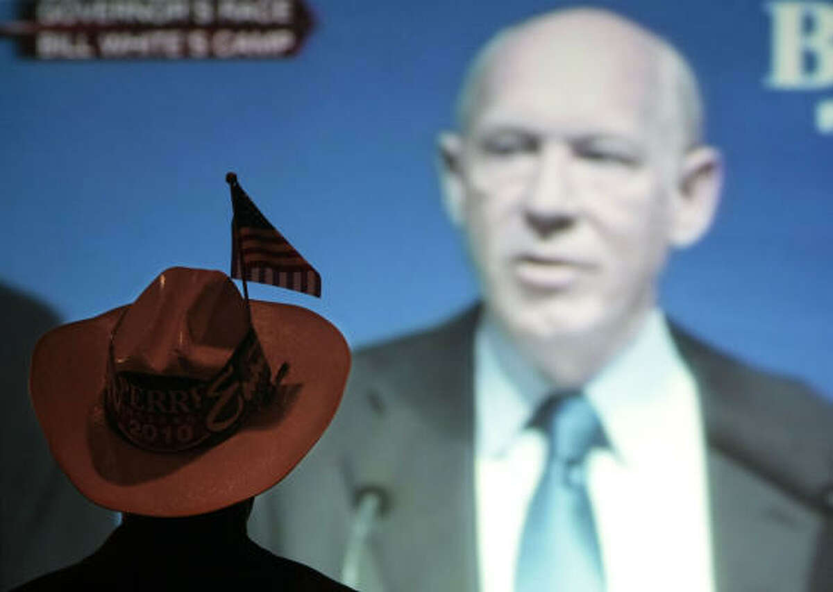 Muyi Arowosafe wearing a cowboy hat outfitted with Rick Perry and Ed Emmett bumper stickers and an U.S. flag stands in front of a monitor at at Judge Ed Emmett's victory party at Hotel ZaZa in Houston, Texas. As Democratic gubernatorial candidate Bill White gives his concession speech after loosing to Republican incumbent Gov. Rick Perry.