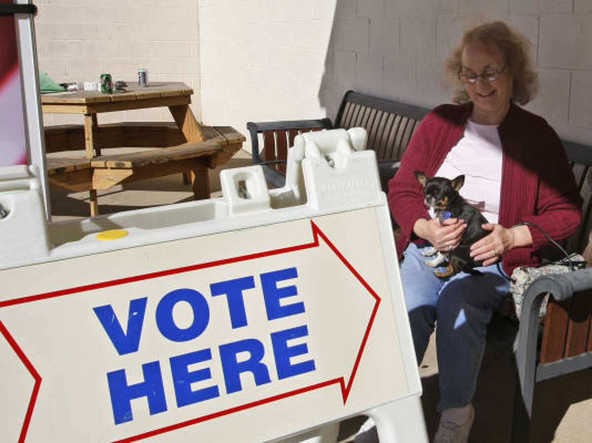 Jewel Welch, of Oklahoma City, holds a dog for a voter who wasn't allowed to take her inside.