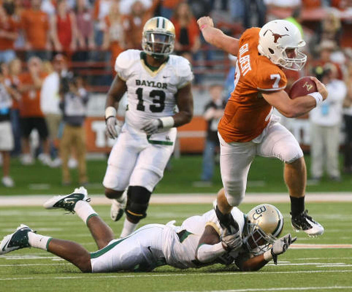 Longhorns quarterback Garrett Gilbert slips past Baylor linebacker Antonio Johnson, bottom left, in the first half.