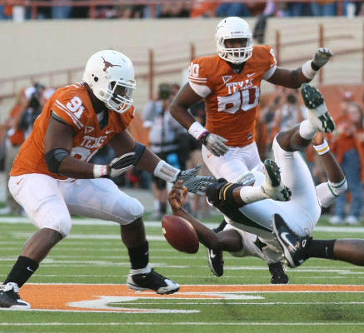Baylor quarterback Robert Griffin III, right, fumbles near Texas defensive tackle Kheeston Randall (91) and Alex Okafor (80) during the first half.
