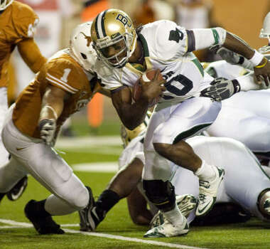Baylor quarterback Robert Griffin III, right, breaks through the Texas defense during third quarter action. Photo: Harry Cabluck, AP