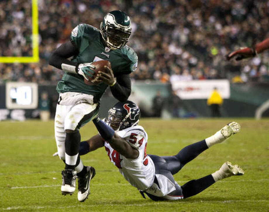Eagles quarterback Michael Vick shakes off Texans linebacker Zac Diles on a run in the fourth quarter. Photo: Brett Coomer, Chronicle