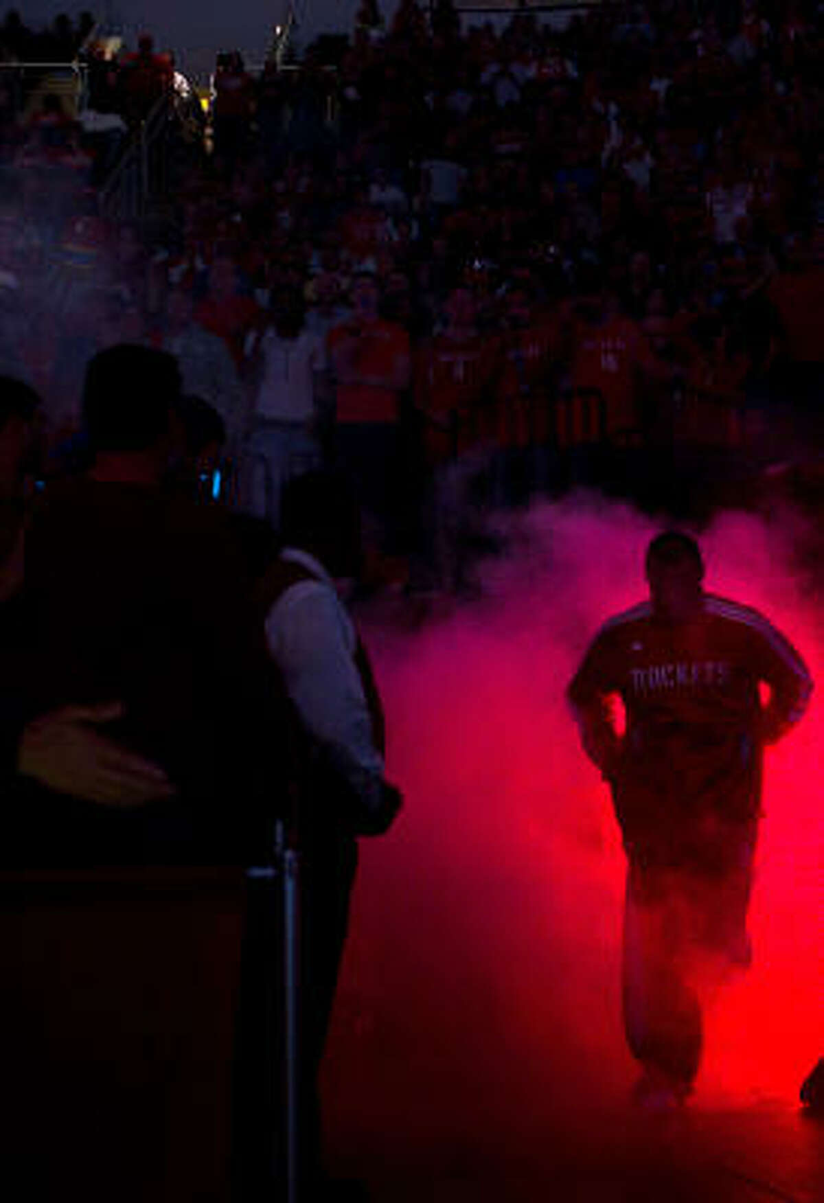Rockets center Chuck Hayes runs through a cloud of smoke as he takes the court for the team's season opener.