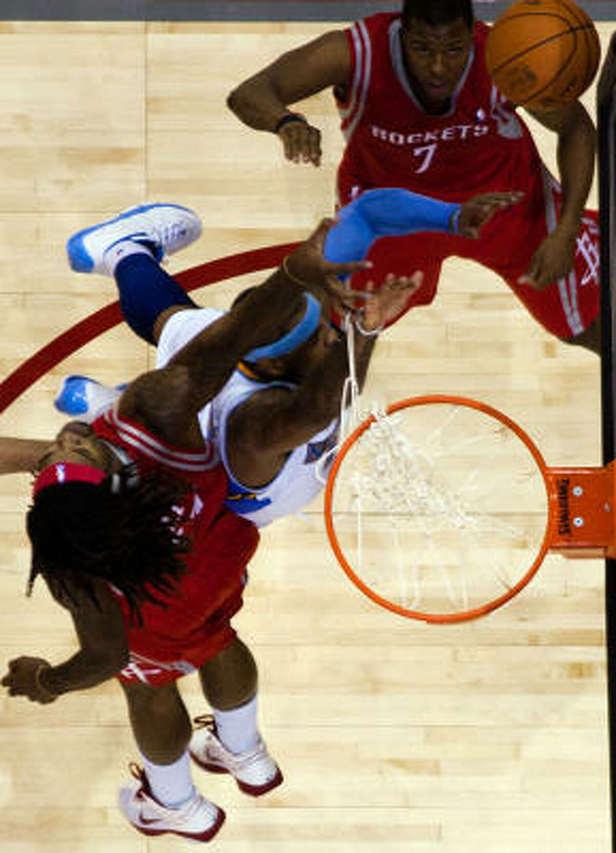 Rockets forward Jordan Hill gets tangled in the net as he fouls Nuggets small forward Carmelo Anthony as Rockets point guard Kyle Lowry (7) looks on during the fourth quarter.