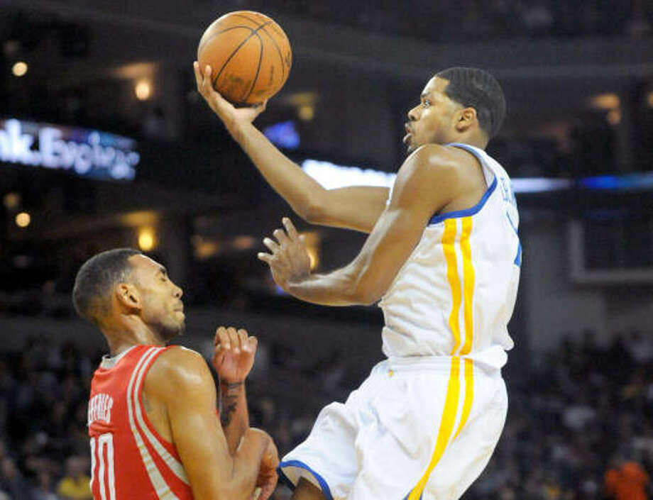 Rockets forward Jared Jeffries, left, tries to block a layup from Golden State's Rodney Carney during the second quarter of Wednesday's game at the Oracle Arena in Oakland, Calif. Photo: DOUG DURAN, MCT