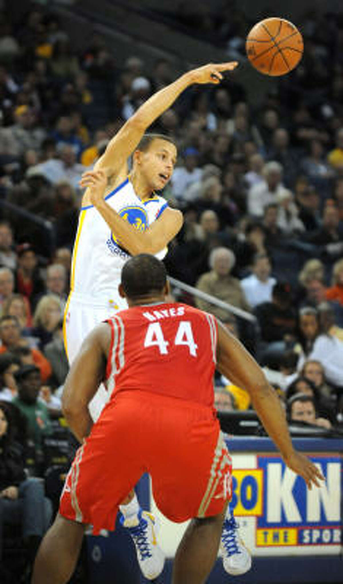 Rockets forward Chuck Hayes (44) watches as Golden State's Stephen Curry makes a pass in the second quarter.