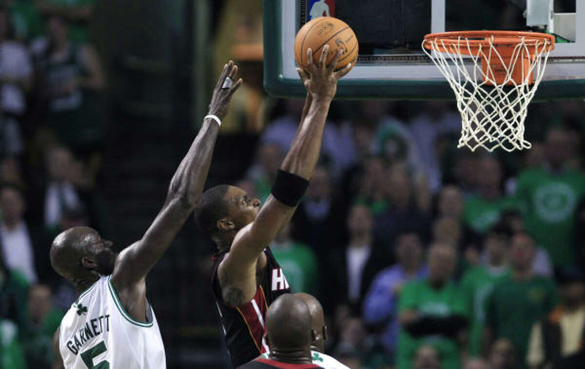 Heat forward Chris Bosh, right, gets past Celtics forward Kevin Garnett on a drive to the basket during the first half.