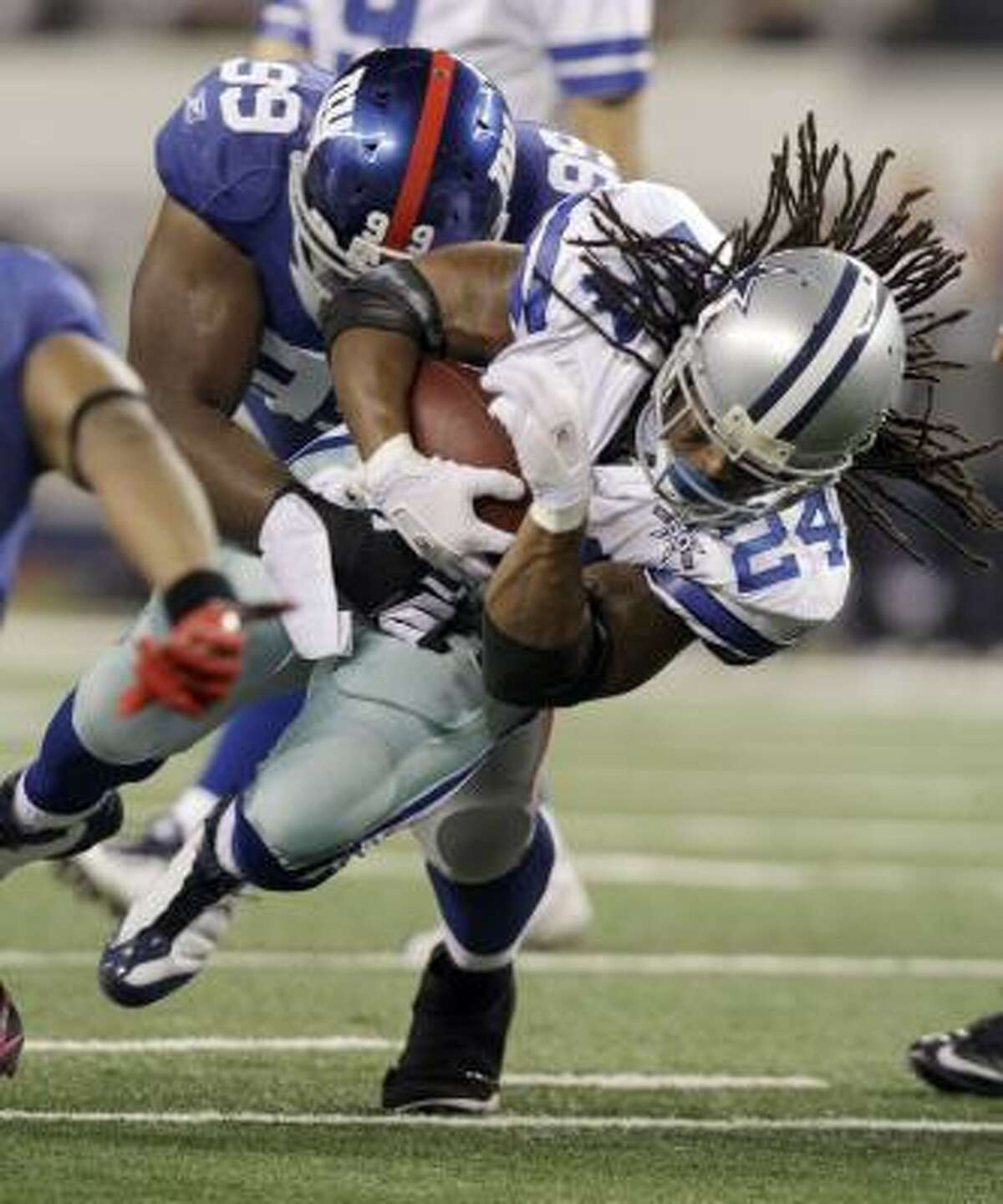 Cowboys running back Marion Barber is stopped by Giants defensive tackle Chris Canty.