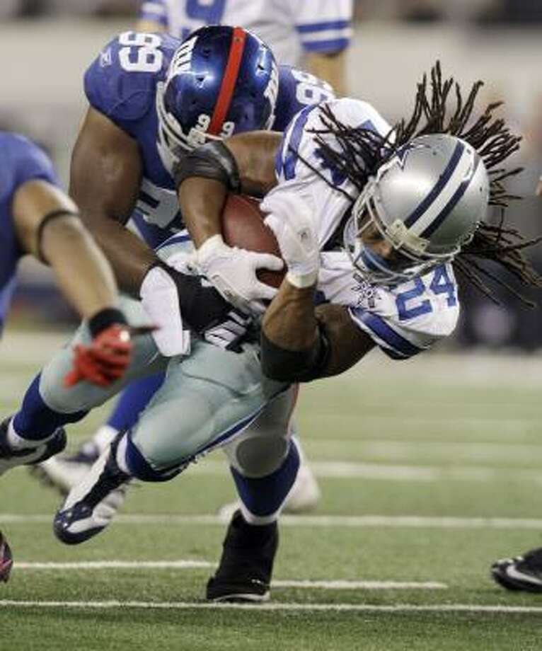 Cowboys running back Marion Barber is stopped by Giants defensive tackle Chris Canty. Photo: LM Otero, AP