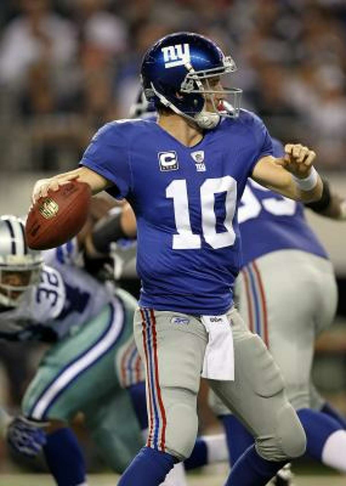 Giants quarterback Eli Manning looks to pass against the Cowboys.