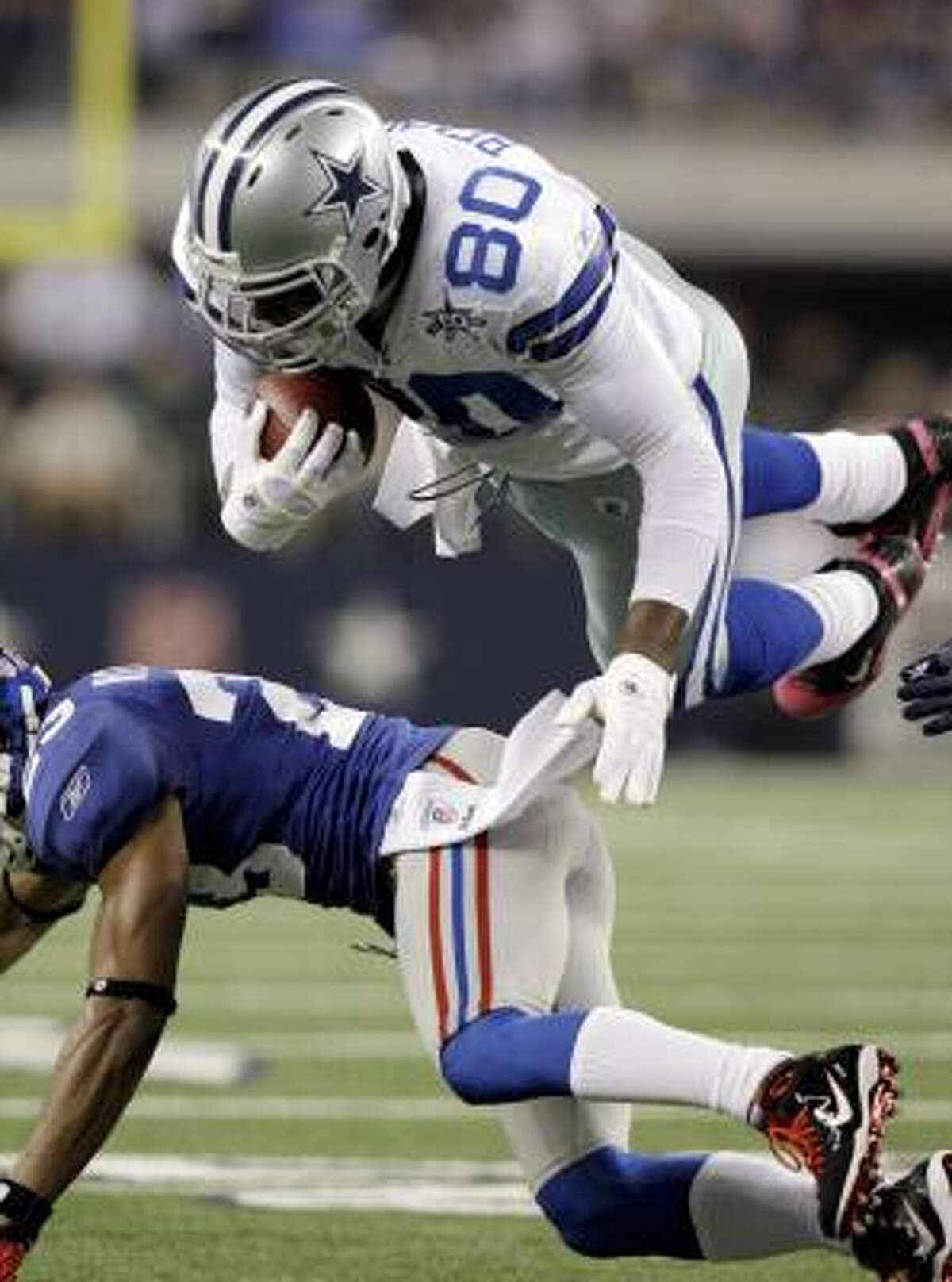 Cowboys tight end Martellus Bennett is upended by Giants cornerback Corey Webster.