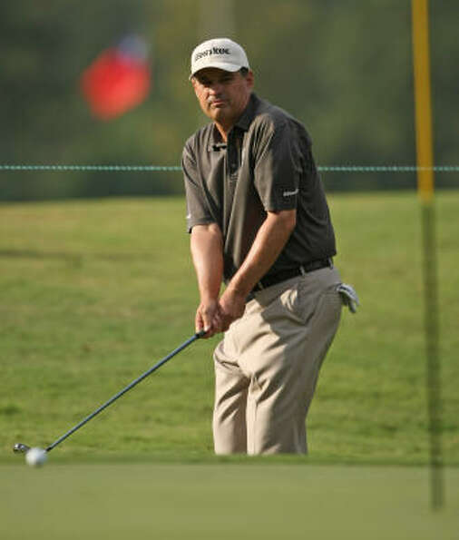 Loren Roberts watches his chip shot onto the ninth green.