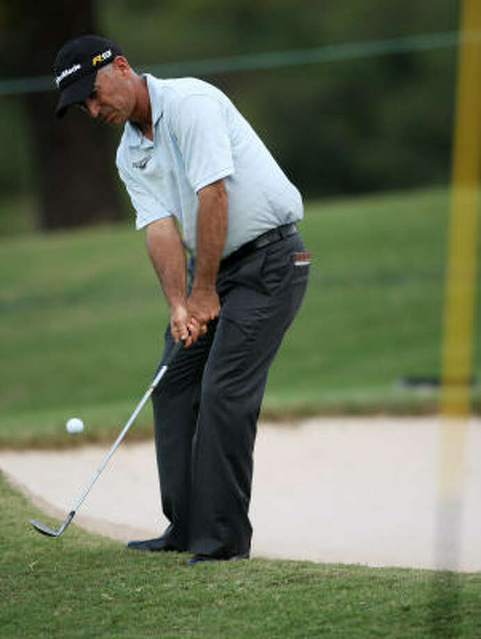 Corey Pavin chips onto the 17th green during the first round. Photo: ERIC CHRISTIAN SMITH, For The Chronicle