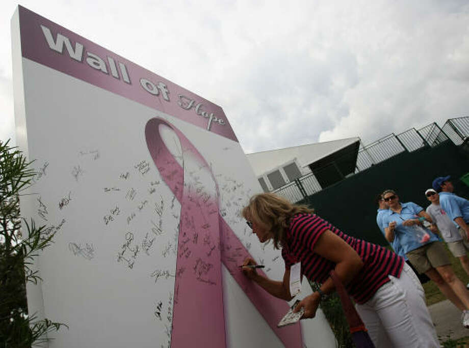 "With October being Breast Cancer Awareness month, Cecelia Lesso signs her name on the ""Wall Of Hope"" during the first round of play. Photo: ERIC CHRISTIAN SMITH, For The Chronicle"