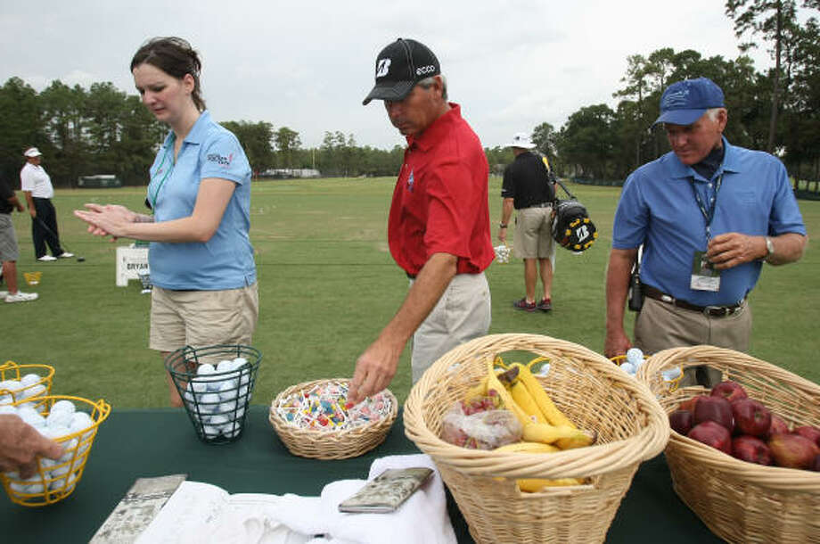 Fred Couples, center, grabs some tees before warming up on the practice tee. Photo: ERIC CHRISTIAN SMITH, For The Chronicle