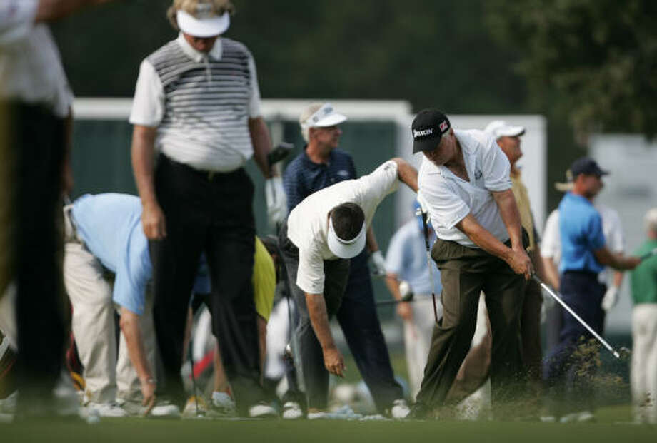 Mark Calcavecchia, swinging on the right, warms up with other Champions Tour players. Photo: ERIC CHRISTIAN SMITH, For The Chronicle