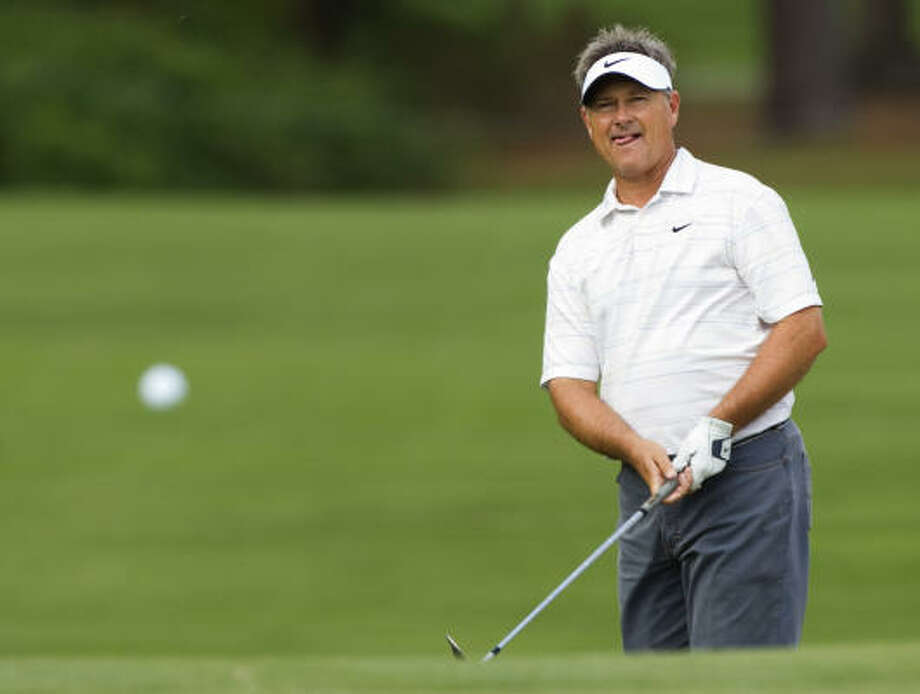 Defending champion John Cook watches his ball after chipping onto the No. 6 green. Photo: Brett Coomer, Chronicle