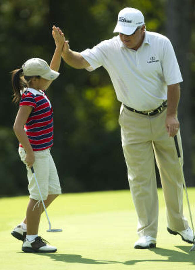 Mark O'Meara high fives Grace Ni, 9, after she hit a birdie putt on the 14th green during The Woodlands Development Company Junior Pro-Am on Tuesday. Photo: Brett Coomer, Houston Chronicle