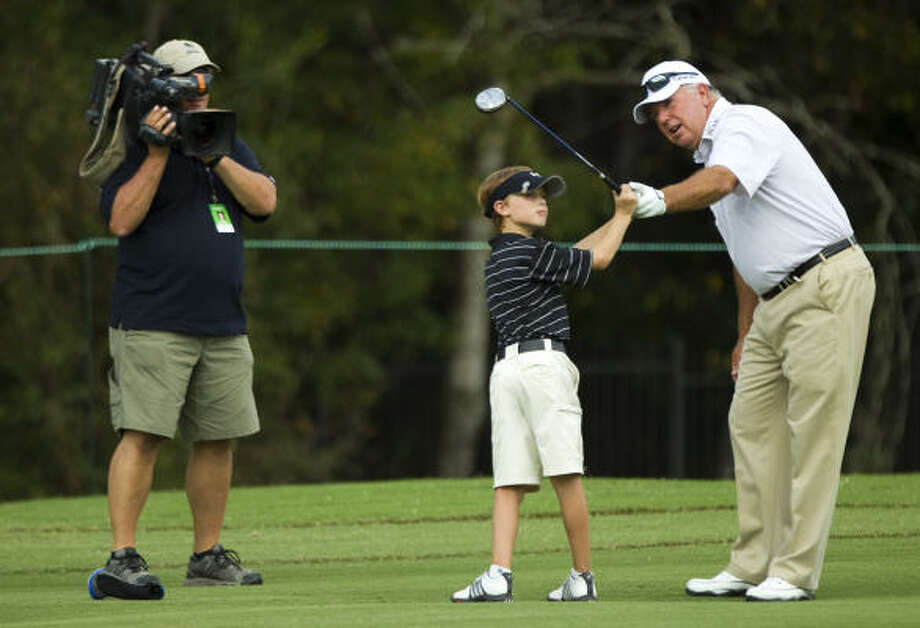 Mark O'Meara helps William Moll with his swing on the 15th fairway during The Woodlands Development Company Junior Pro-Am on Tuesday. Photo: Brett Coomer, Houston Chronicle