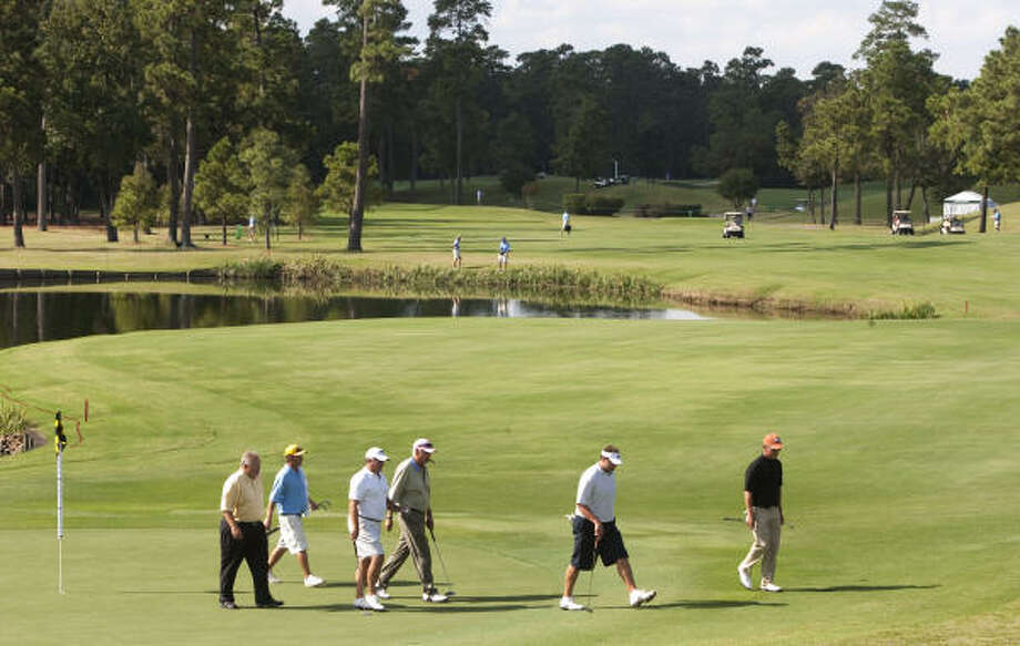 John Jacobs' group walks off the 18th green during United Health Care Pro-Am on Monday. Photo: Brett Coomer, Houston Chronicle