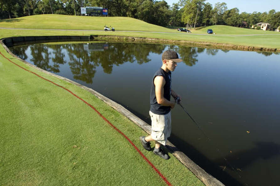 Kenny Fetters spends his morning fishing in the water hazard near the 17th green on Monday.