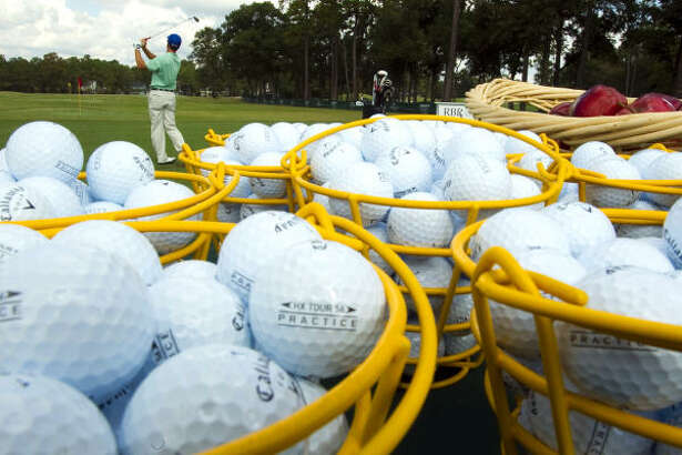 Bobby Clampett hits golf balls on the driving range as he gets ready for the United Health Care Pro-Am on Monday.