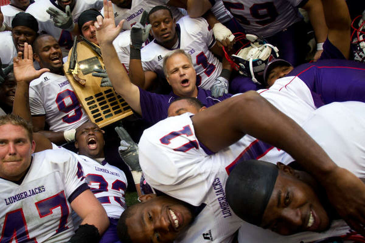 Stephen F. Austin players crowd around head coach J.C. Harper as they celebrate with the Battle of the Piney Woods trophy after defeating Sam Houston State.