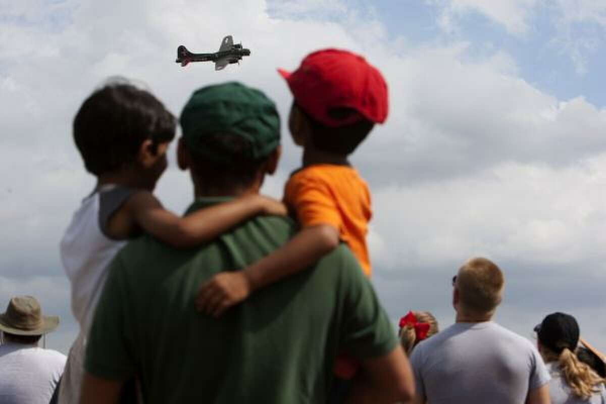 Getting a good look at a B-17, Dhruv, 5, and Mihir, 4, Balivada of Sugar Land, hold onto their father, Suresh Balivada during the 26th annual Wings Over Houston Airshow at Ellington Airport.