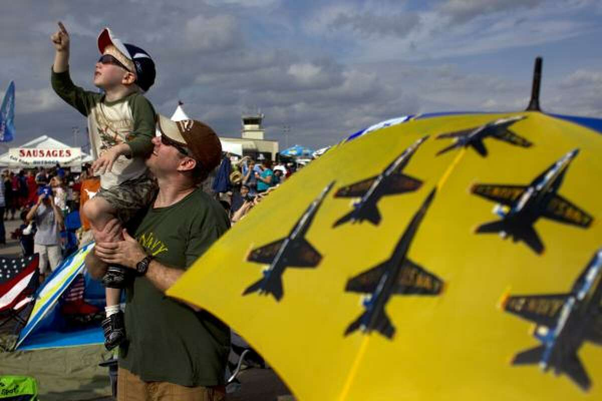 Sean Fuller, 4, looks up for airplanes as he is held by his father, Eric Fuler, 40, of Spring.