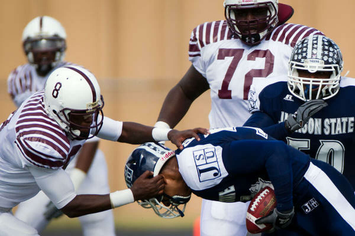 Texas Southern quarterback Arvell Nelson (8) tackles Jackson State defensive end Donavan Robinson (54) after Robinson recovered a fumble during the first half.