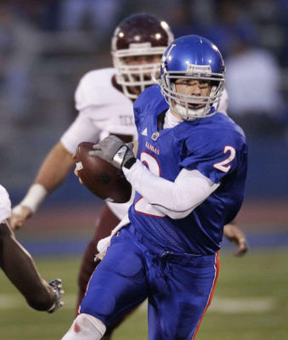 Kansas quarterback Jordan Webb runs away from Texas A&M defensive tackle Lucas Patterson for a 25-yard gain during the first half.