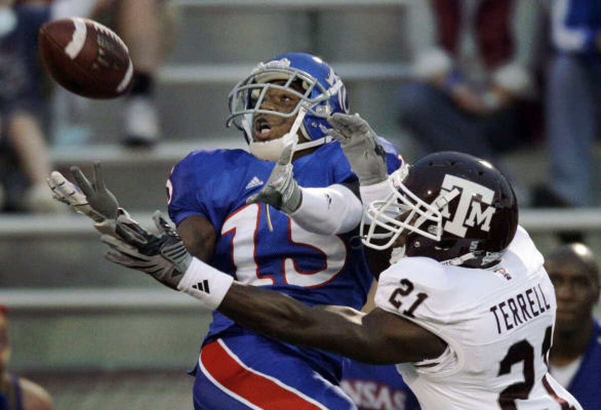 Kansas running back Daymond Patterson (15) and Texas A&M cornerback Steven Terrell (21) battle for the ball during the first half.