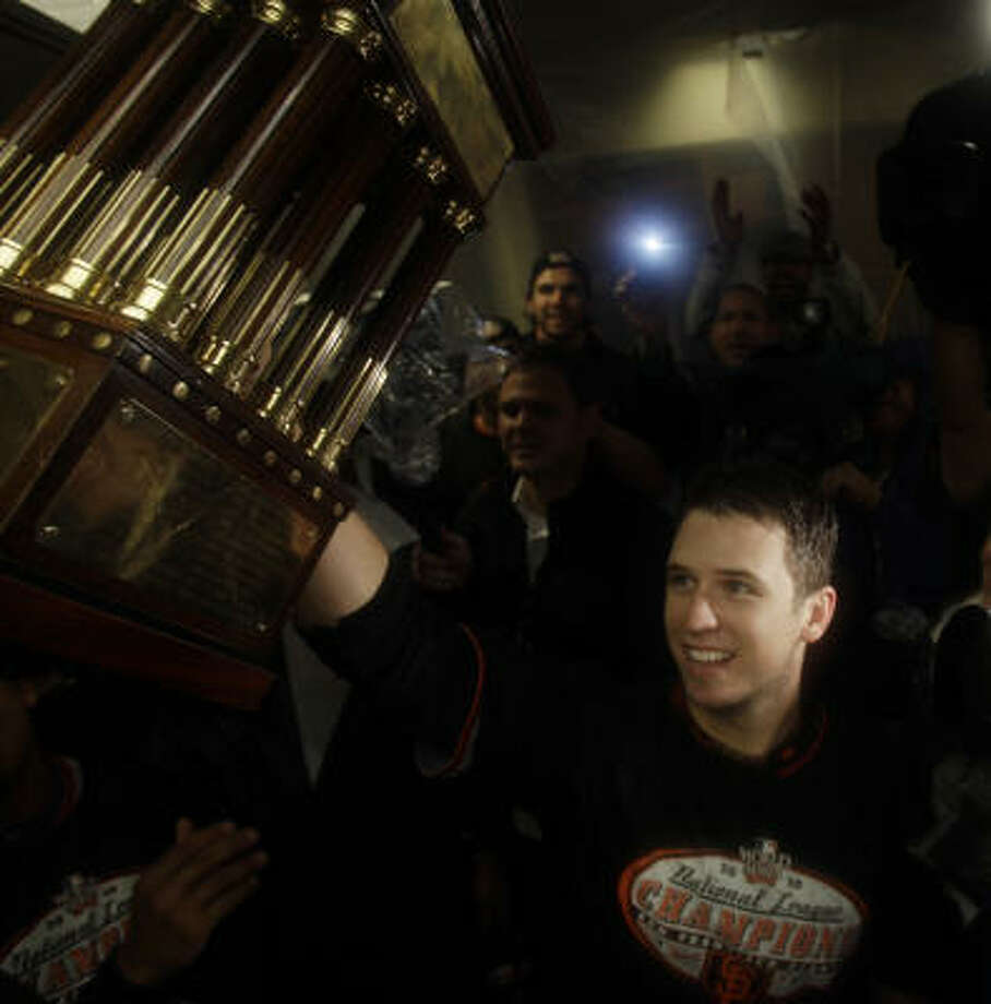 The  Giants' Buster Posey holds up the championship trophy after Game 6 of the NLCS. Photo: David J. Phillip, AP
