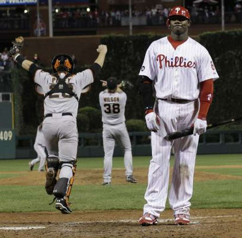 The San Francisco Giants rush the field as Philadelphia Phillies' Ryan Howard stands dejected, as he will not be going to the World Series. Photo: David J. Phillip, AP