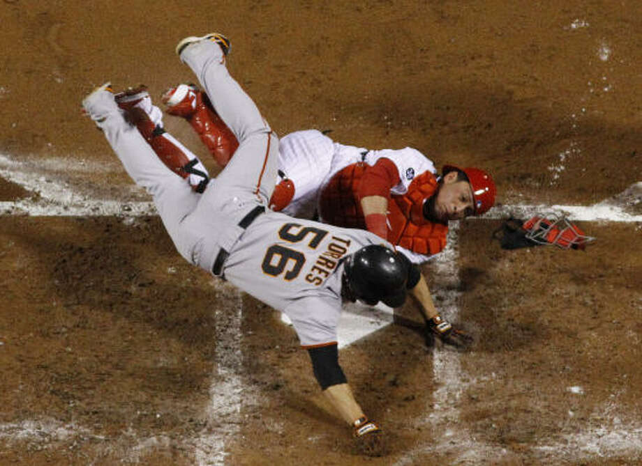 The Giants' Andres Torres (56) collides with Phillies catcher Carlos Ruiz as he tries to score on a hit by Aubrey Huff during the third inning of Game 6 of the NLCS. Photo: Matt Slocum, AP