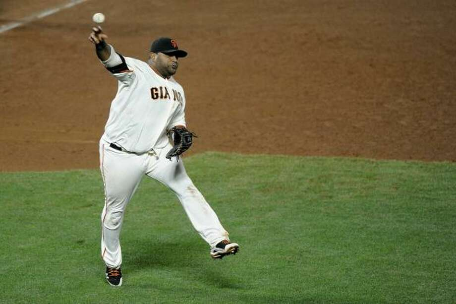 Giants third baseman Pablo Sandoval makes an errant throw in the ninth inning. Photo: Harry How, Getty Images