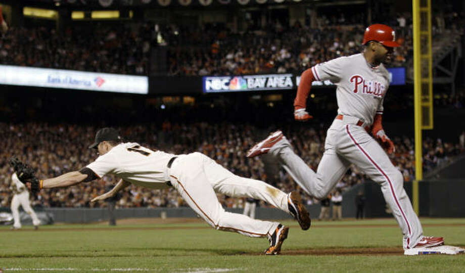 Giants first baseman Aubrey Huff dives for an errant throw as Philadelphia's Ben Francisco reaches safely in the ninth inning. Photo: David J. Phillip, AP