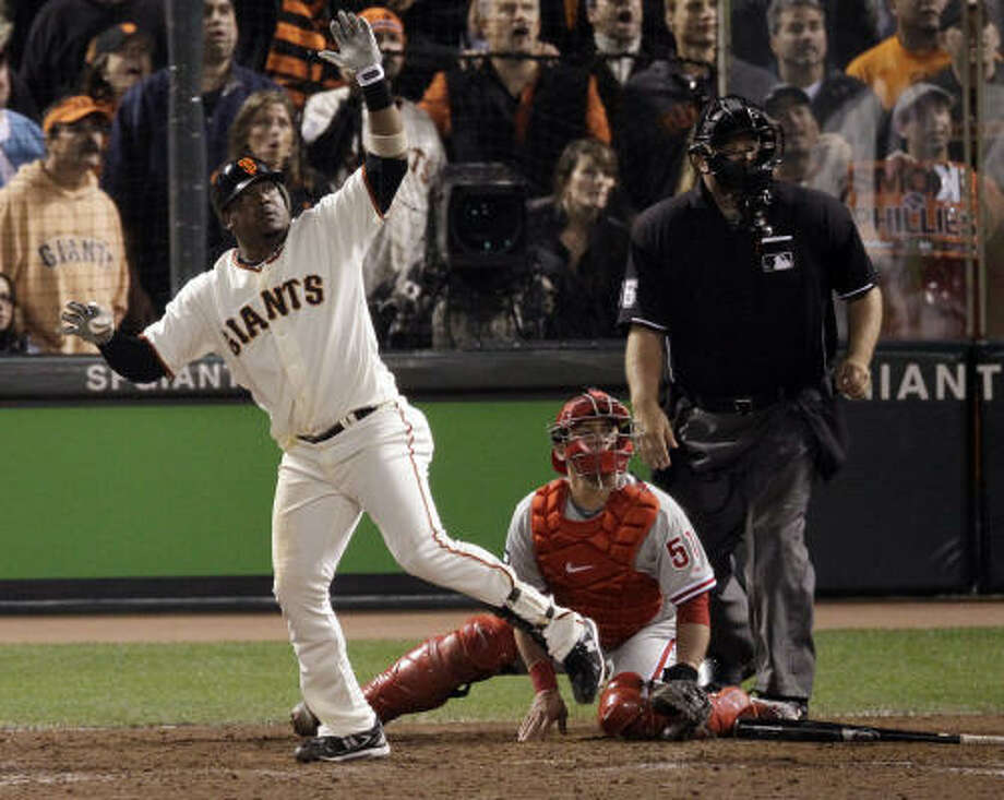 San Francisco's Juan Uribe watches the flight of his game-winning sacrifice fly during the ninth inning. Photo: Marcio Jose Sanchez, AP