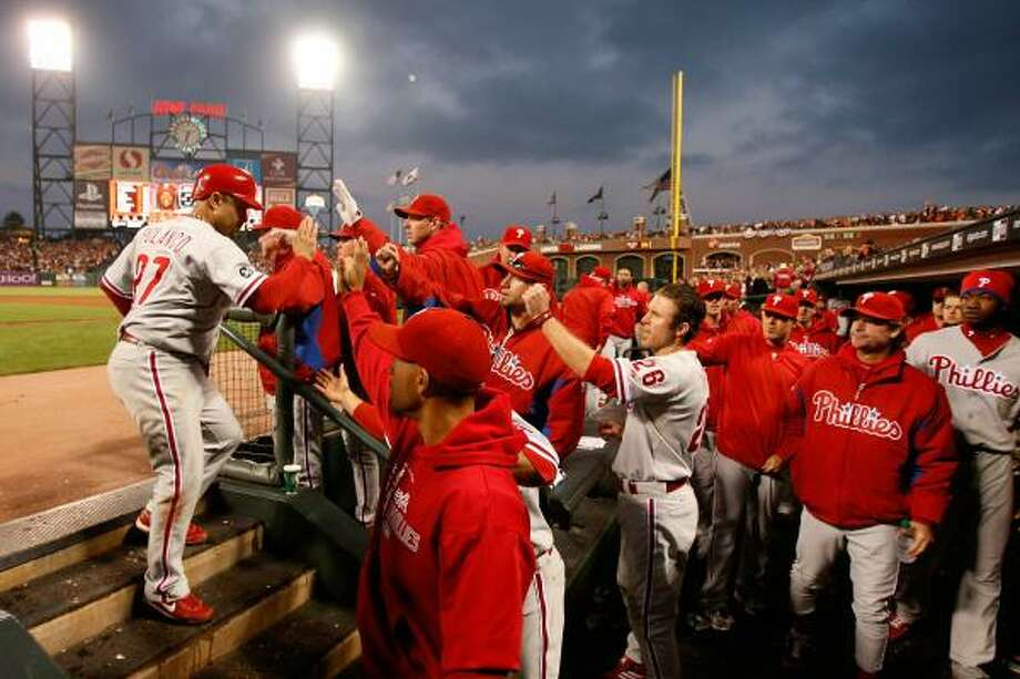 Philadelphia's Placido Polanco (27) celebrates with teammates in the dugout after scoring in the fifth inning. Photo: Harry How, Getty Images