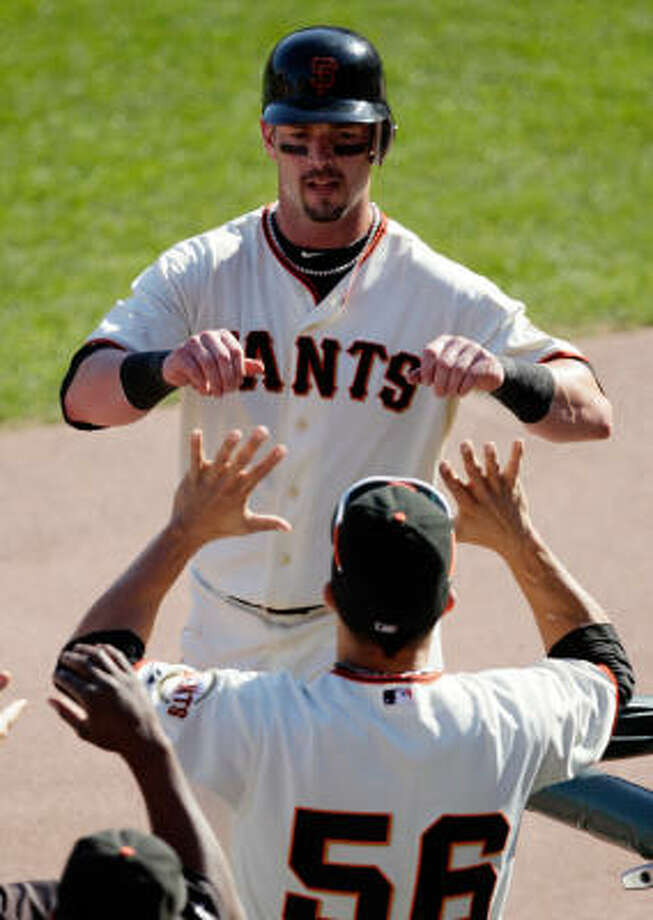 Giants outfielder Aaron Rowand is congratulated by Andres Torres (56) after Rowand scored on an error by Philadelphia Phillies' Chase Utley. Photo: Ben Margot, AP