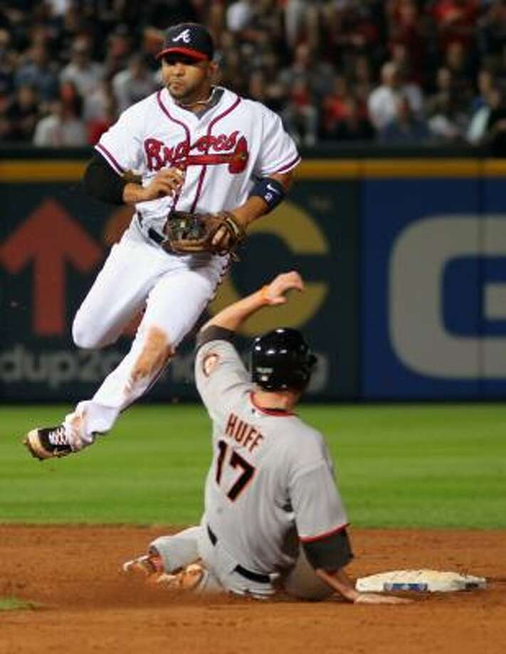 Braves shortstop Alex Gonzalez turns a double play as Giants first baseman Aubrey Huff approaches second during the ninth inning. Photo: Jamie Squire, Getty Images